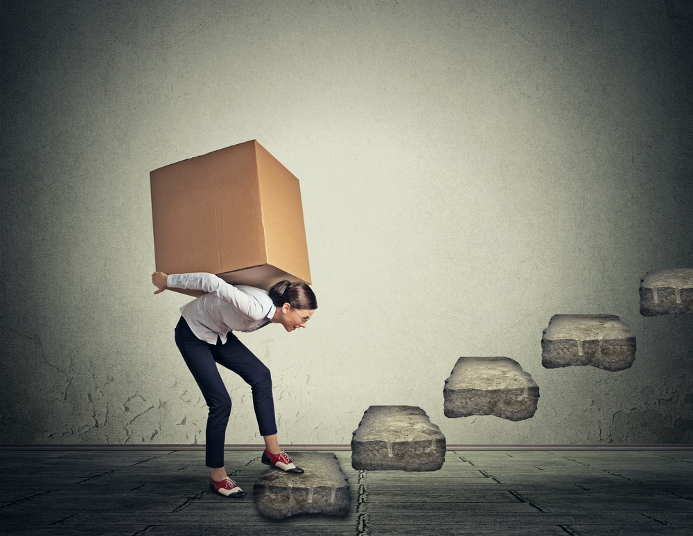 Difficult task perspective concept. Young slim woman carrying large heavy box on her back upstairs
